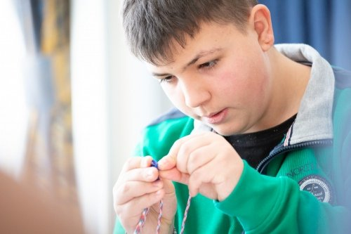 Дима Бакланов занимается плетением браслета