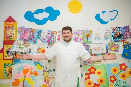 На фоне стены с детскими рисунками в отделении