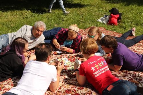 Волонтеры и сотрудники фонда играют на траве в настольные игры